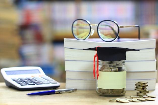 Sombrero de graduación en la botella de vidrio en el estante de la biblioteca, ahorrando dinero por concepto de educación