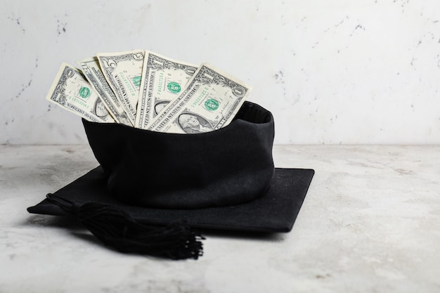 Sombrero de graduación con dinero en la mesa. concepto de tasas de matrícula