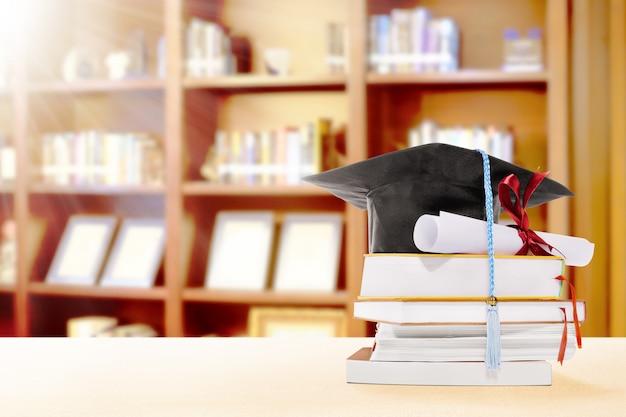 Sombrero de graduación, diploma de desplazamiento y libros sobre la mesa con estantería