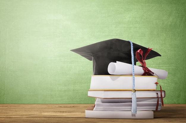 Sombrero de graduación, diploma de desplazamiento y libros sobre la mesa de madera