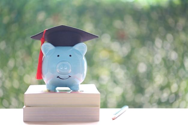 Sombrero de graduación en la hucha con fondo verde de la naturaleza, ahorrando dinero para el concepto de educación
