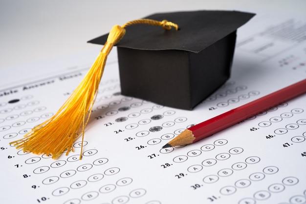 Sombrero de graduación y lápiz sobre fondo de hoja de respuestas