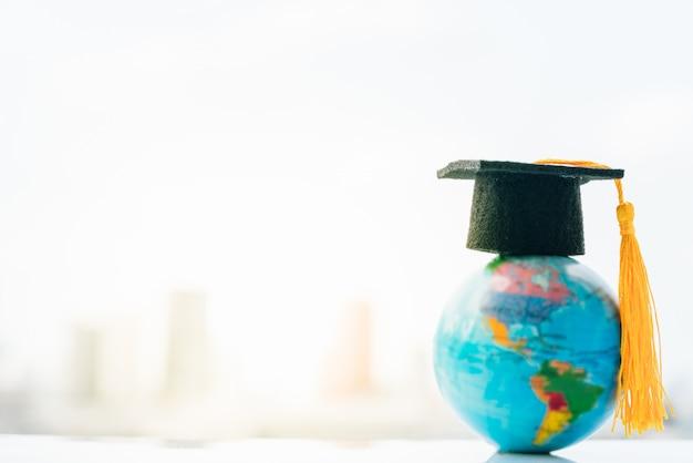 Sombrero de graduación en mapa de modelo de globo de tierra superior con fondo de ciudad.