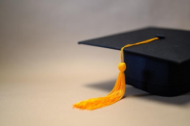 Sombrero de graduación negro colocado sobre papel marrón