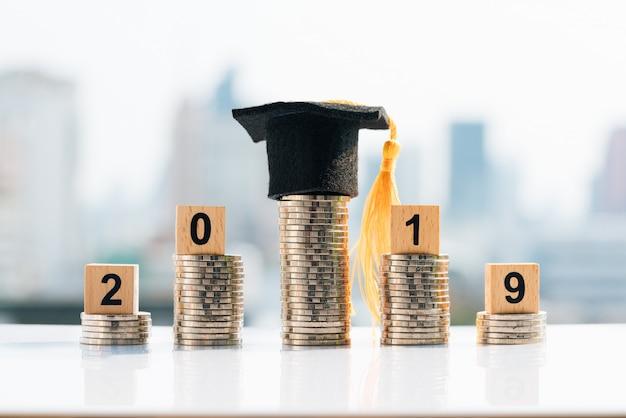 Sombrero de graduación en la pila de monedas superior con 2019 bloques de madera.