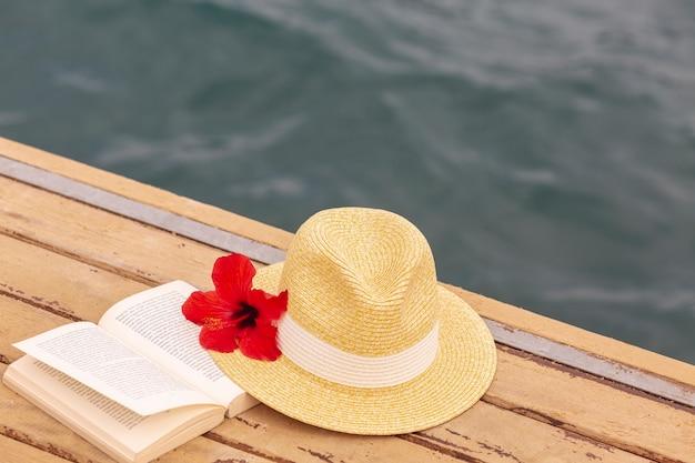 Sombrero y libro en el muelle