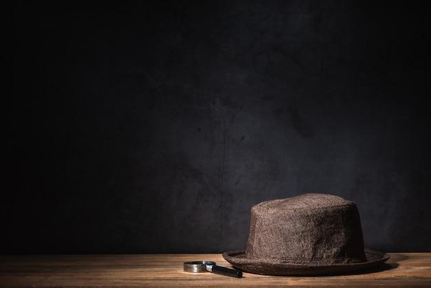 Sombrero marrón y lupas en mesa de madera