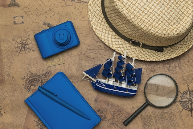 Un sombrero, un modelo de barco, una cámara y un cuaderno sobre un mapa antiguo. el concepto de planificación de viajes.