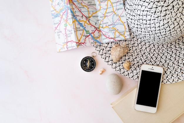 Sombrero de mujer con accesorios de viaje y mapa.