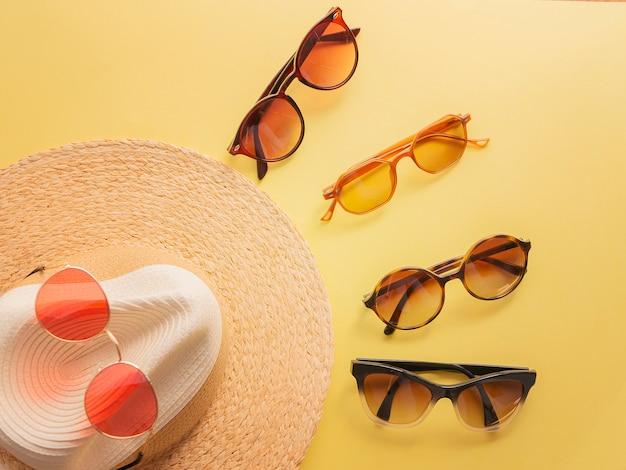 Sombrero de mujer de paja con lentes de sol vista superior fondo amarillo brillante plano, solo