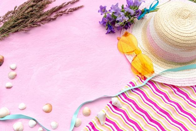 Sombrero de mujer de verano con flores, gafas de sol, toalla y conchas marinas
