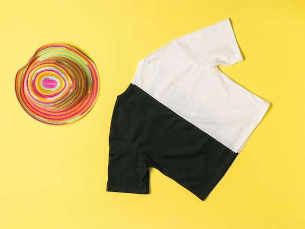 Un sombrero multicolor y una camiseta en blanco y negro sobre una superficie amarilla.