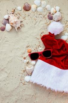 Sombrero de navidad y gafas de sol rojas en la playa.