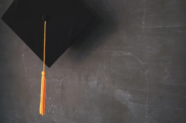 Sombrero negro de graduados colgado en la pizarra.