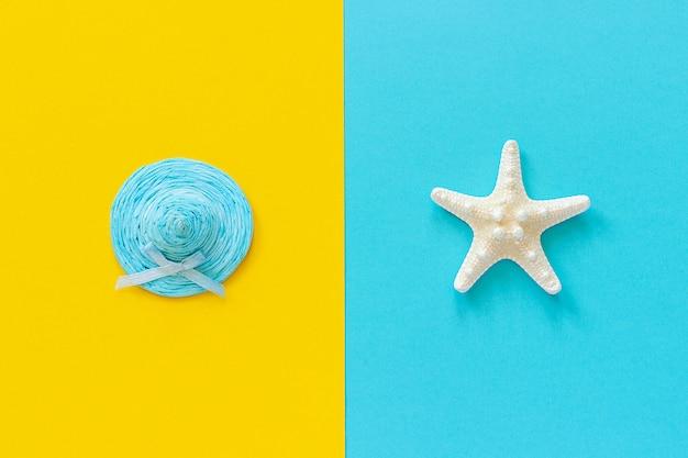 Sombrero de paja azul en papel amarillo y estrellas de mar sobre fondo azul