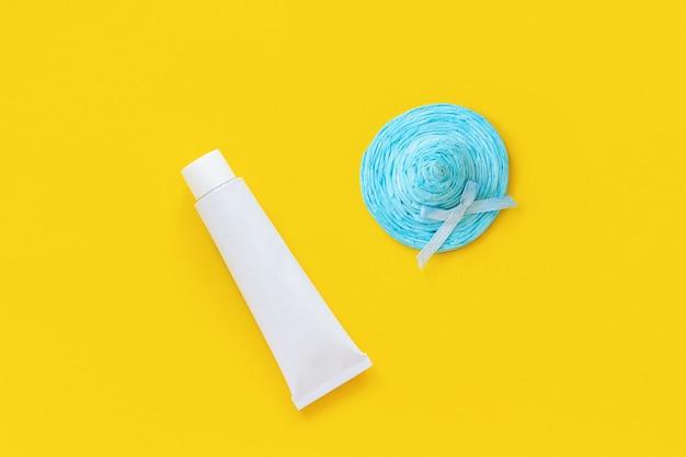 Sombrero de paja azul y tubo blanco de protector solar sobre fondo de papel amarillo