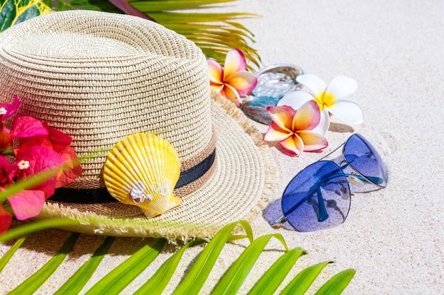Sombrero de paja beige con gafas de sol azules, conchas de mar de colores, flores de frangipani y hojas de palma verde sobre arena.