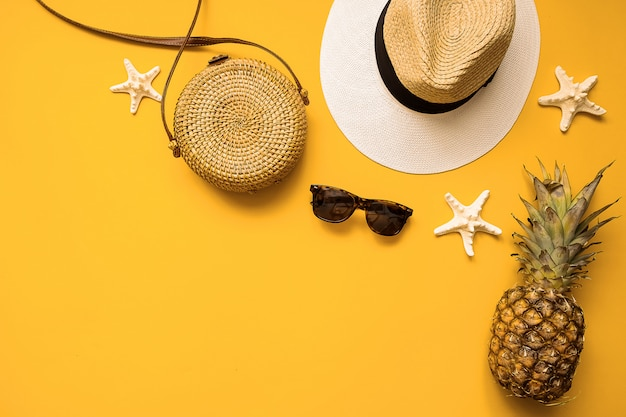 Sombrero de paja, bolsa de bambú, gafas de sol, piña y estrellas de mar sobre amarillo