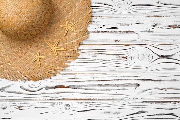 Sombrero de paja con estrellas de mar sobre superficie de madera