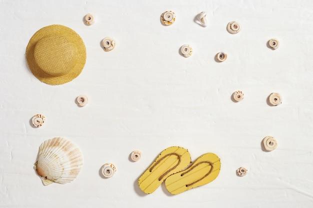 Sombrero de paja y flip-flop en el fondo blanco con el espacio de la copia. concepto de vacaciones en la playa.