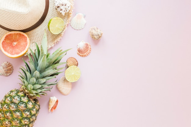 Sombrero de paja con frutas exóticas y conchas.
