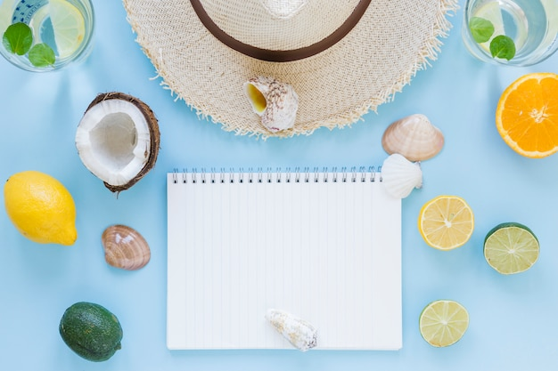Sombrero de paja con frutas exóticas y cuaderno.