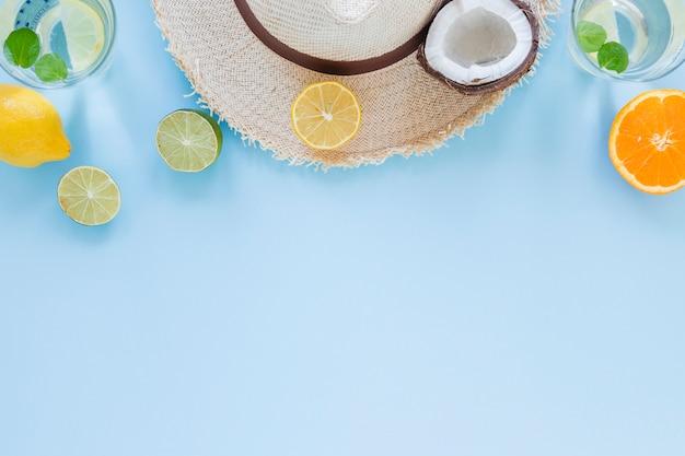 Sombrero de paja con frutas exóticas en mesa.