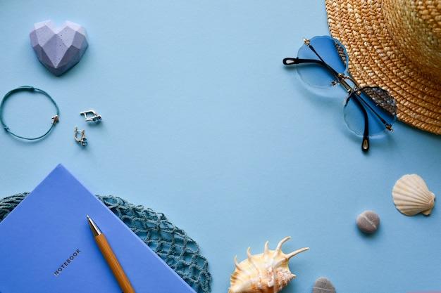Sombrero de paja, gafas de sol, bloc de notas con bolígrafo de madera, bolso de hilo, joyas de mujer, conchas y guijarros sobre un fondo de papel azul. vista superior. endecha plana.