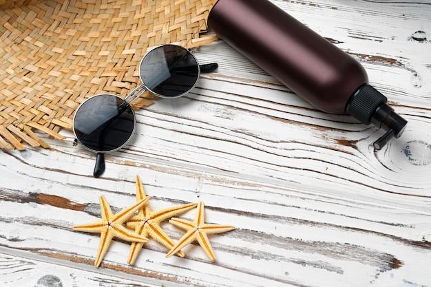 Sombrero de paja, gafas de sol y botella de protector solar sobre fondo de madera