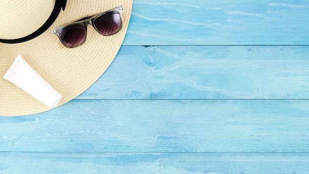 Sombrero de paja con gafas de sol y crema de protección solar.