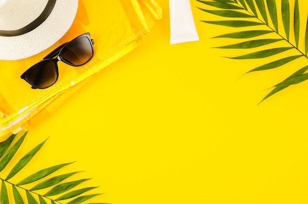 Sombrero de paja con gafas de sol y hojas de palmera.