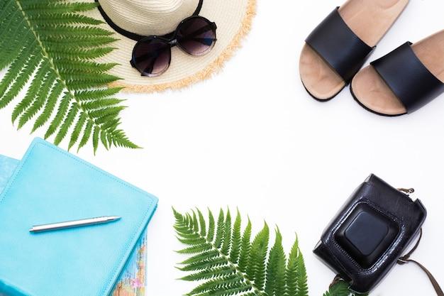 Sombrero de paja, gafas de sol, mapa, cámara, hoja de helecho en blanco