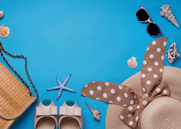 Sombrero de paja, gafas de sol y zapatos sobre fondo azul