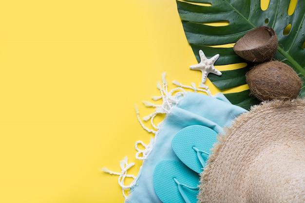 Sombrero de paja de playa, cocos, concha y hojas de monstera. vacaciones de verano con accesorios. vista superior.