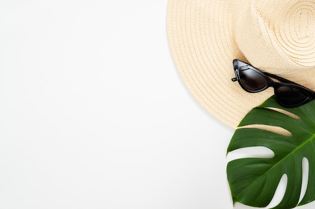 Sombrero de paja de playa, gafas de sol y hoja de palma monstera tropical sobre fondo blanco.
