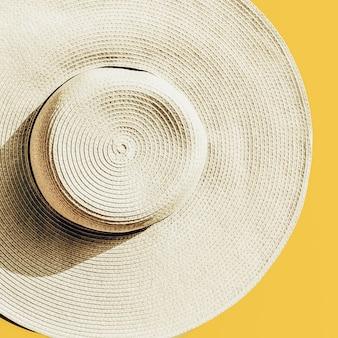 Sombrero de paja sobre fondo soleado amarillo brillante