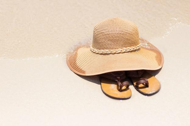Sombrero de paja y zapatos en la playa en verano.