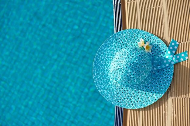 Sombrero de playa junto a la piscina, vista superior con espacio para el texto.