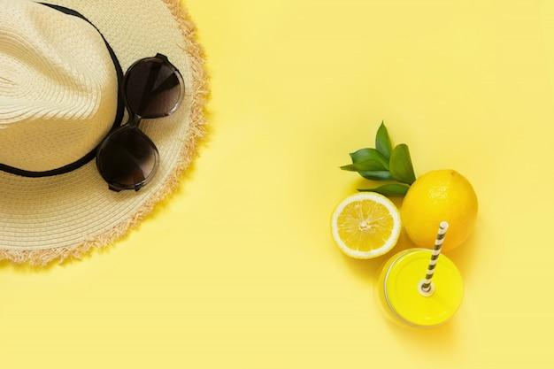 Sombrero de playa de paja y gafas de sol negras con agua de cítricos en amarillo. vista superior. lay flat.