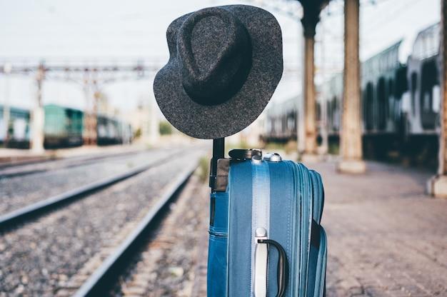 Sombrero posado sobre una maleta en una estación de tren.