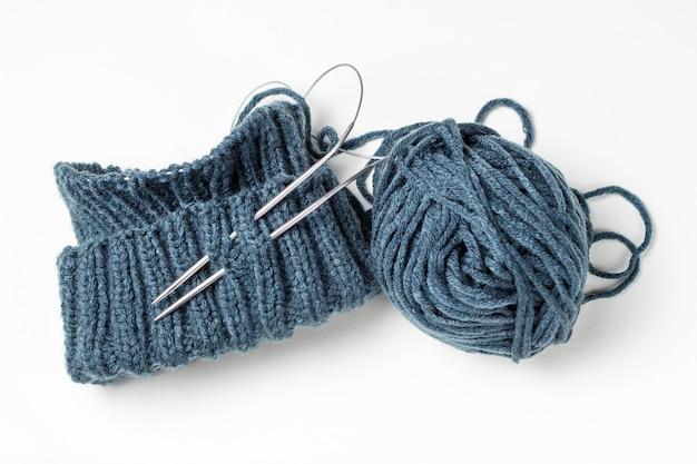 Sombrero de punto, agujas de tejer y madeja sobre fondo blanco.