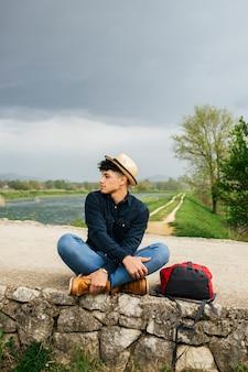 Sombrero que lleva del hombre que se sienta cerca del río hermoso