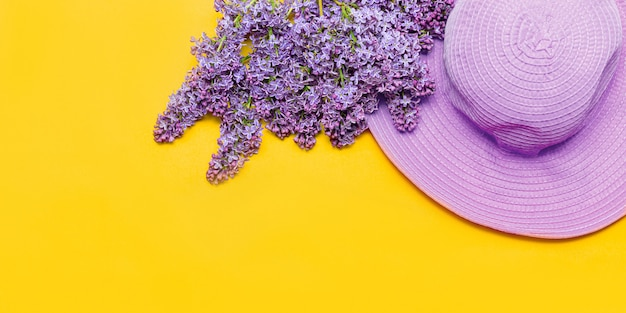 Sombrero rosa de verano para mujer y ramo de flores lilas.