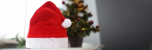 Sombrero de santa claus de pie cerca del árbol de navidad closeup