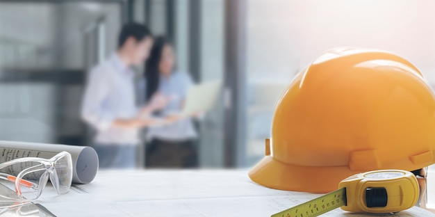 Sombrero de seguridad amarillo y herramientas de ingeniería sobre la mesa con fondo de imagen borrosa de la reunión del equipo de ingenieros.