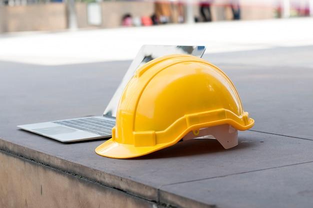 El sombrero de seguridad y la computadora están en el sitio de construcción