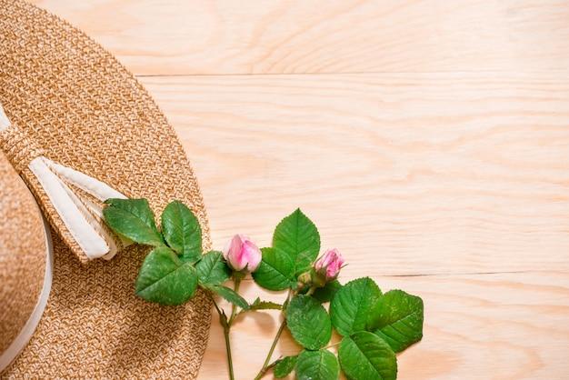 Sombrero para el sol y margaritas en tablón de madera