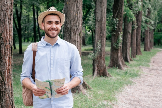 Sombrero sonriente de la tenencia del sombrero del hombre que lleva joven en parque