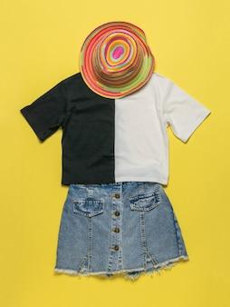 Sombrero de verano, camiseta y falda de mezclilla sobre una superficie amarilla