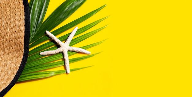 Sombrero de verano con estrellas de mar en hojas de palmeras tropicales con sobre fondo amarillo.